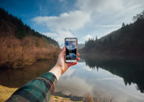 GlobalReach-man using phone by lake